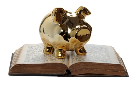 golden piggy bank on old book on white photo