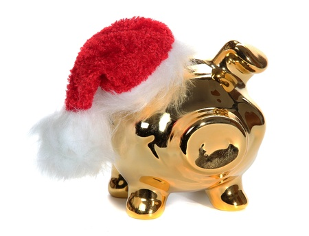 christmas savings: golden piggy bank with red jelly bag cap