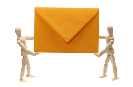 two wooden dolls holding yellow envelope Stock Photo