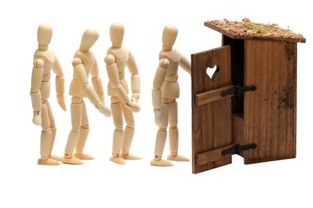 latrine: wooden dolls in waiting line Stock Photo
