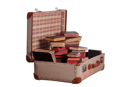 very old suitcase stuffed with old books photo