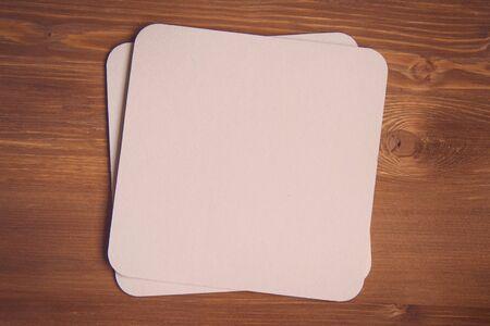 empty blank cardboard beermat on wood mockup 版權商用圖片