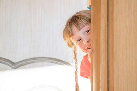a smiling girl looks out from behind the door
