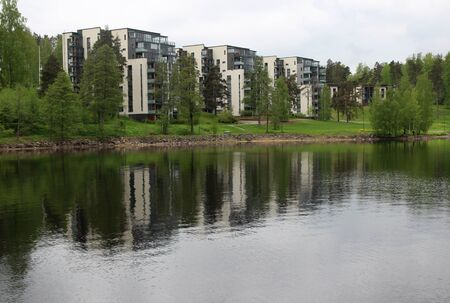Finland Lappeeranta - view of the lake with reflections, beautiful white houses among green trees, spring nature