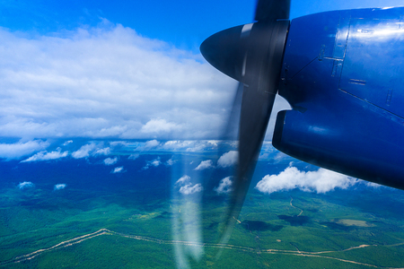 A view of the land from the window of the plane. In the foreground is a working blue propeller. Clear sky with white clouds. Below are small mountains covered with forest. Forest road and shadows from the clouds.