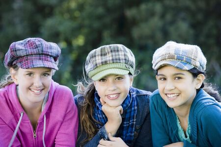Portrait of Three Smiling Tween Girls sitting on the grass wearing plaid hats.