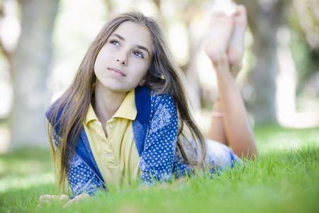 Portrait of Tween Girl Lying on Grass Looking up to Sky