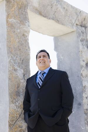 overweight people: Businessman Standing By An Archway Looking Away From Camera Stock Photo