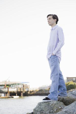 Teenage Boy Standing on Rocks Looking at Water Imagens