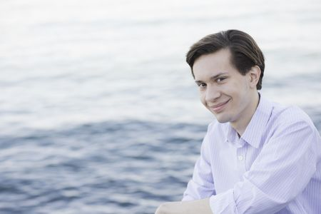 Portrait of Smiling Teenage Boy Sitting by Water Reklamní fotografie