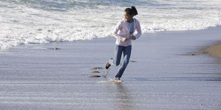 Teenage Asian Girl Running from Waves at Beach photo