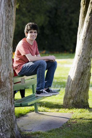 enfant banc: Smiling Teenage Boy assis sur un banc dans le parc