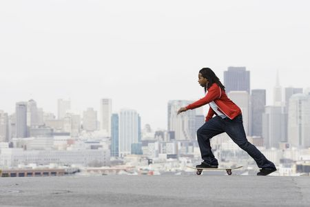 African American Teen Boy on Skateboard in front of City View