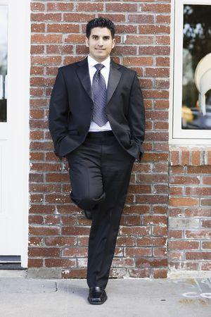 양복 입고 남자 벽돌 벽에 기대어 넥타이 웃고 스톡 콘텐츠