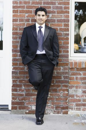 Smiling Man Dressed in Suit and Tie Leaning against Brick Wall