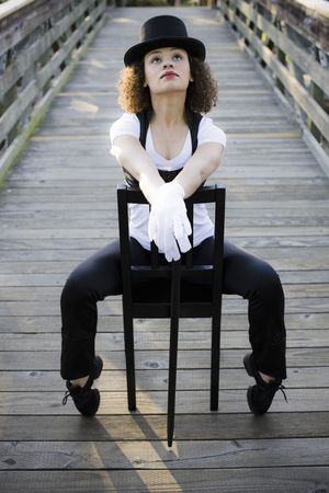 Jazz Dancer in Tophat Sitting in Chair on Bridge Stock Photo