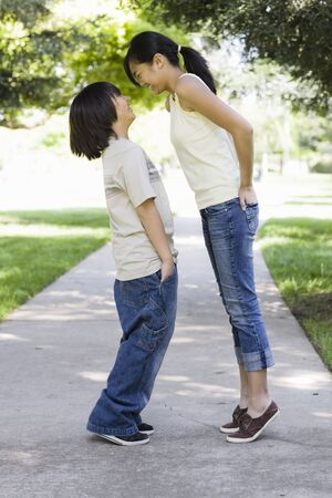 Asian Brother and Sister Standing in a Park