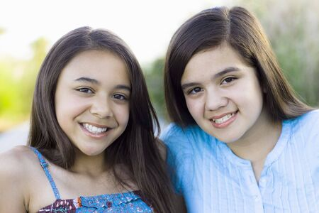 Two Tween Girls in a Park Smiling To Camera Stock Photo