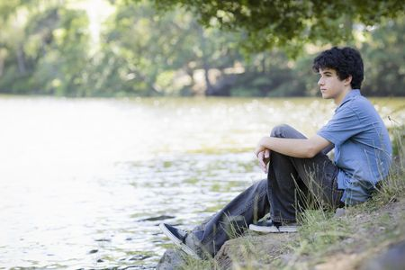 Teen Boy Sitting By lake Looking into Distance Stock Photo