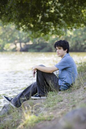 Teen Boy Sitting By lake Looking into Distance Stock Photo - 5667452