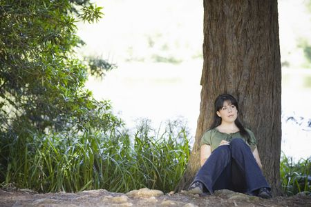 Young Woman sitting by Tree in Woods Writing in Journal Stock Photo