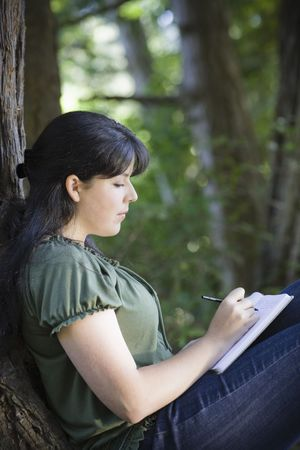 Young Woman Sitting in Woods Writing in Journal Stock Photo