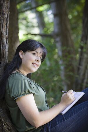 person writing: Young Woman In Woods Writing in Journal Looking Away from Camera