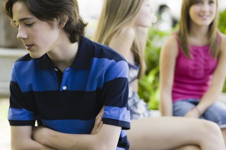 tween boy: Teen Boy Sititing in Park with Two Girls Sitting Behind Him Stock Photo