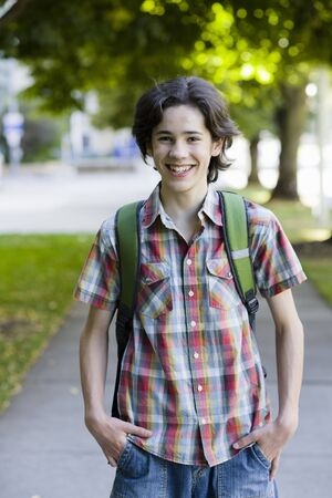 Teenage Boy On Sidewalk in Park Smiling to Camera