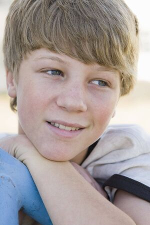 Portrait of Tween Boy Resting Chin on Arm Looking Away From Camera photo
