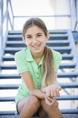 orthodontics: Portrait of Smiling Tween Girl Sitting On Stairway