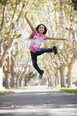 Portrait of Smiling Tween Girl Jumping on Pathway between Trees