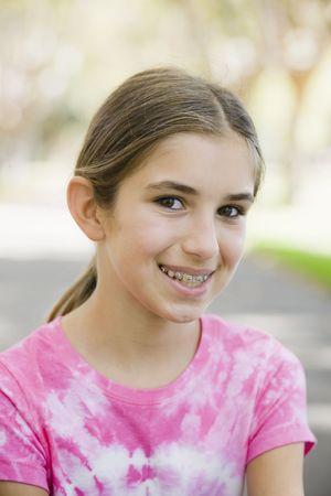 Portrait of Smiling Tween Girl with Braces  Wearing Tye-dyed T-Shirt