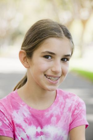 Portrait of Smiling Tween Girl with Braces  Wearing Tye-dyed T-Shirt