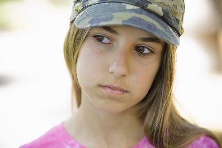 looking away from camera: Portrait of Tween Girl in Cap Looking away from Camera Stock Photo