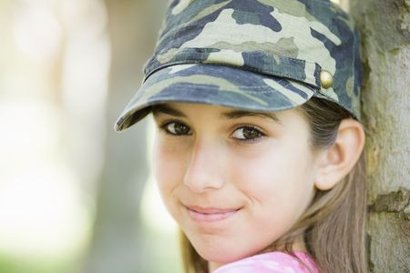 Portrait of Smiling Tween Girl Leaning Against Tree Stock Photo