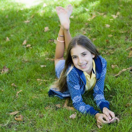 orthodontics: Retrato de Smiling Tween Girl lying on Grass sonriendo a la c�mara