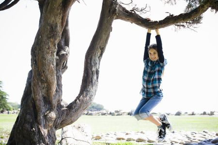 Portrait of Smiling Tween Girl Hanging from a Tree Branch