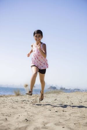 Smiling Young Asian Girl Running on Sand at Beach Stock Photo