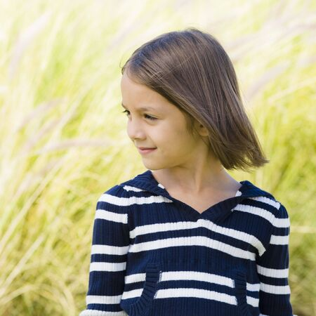 Portrait of A Smiling Young Girl In Striped Sweater Standing in Grass