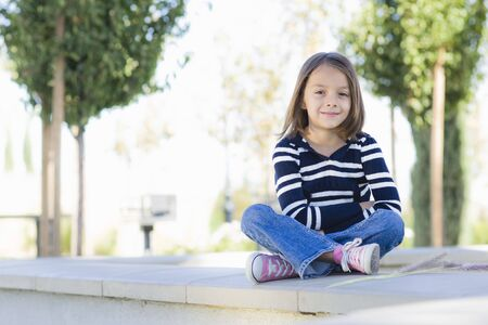Smiling Young Girl In Striped Sweater Sitting on Wall in Park