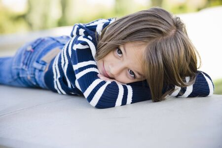 tot: Portrait of Young Girl Lying on Stomach in a Park Stock Photo