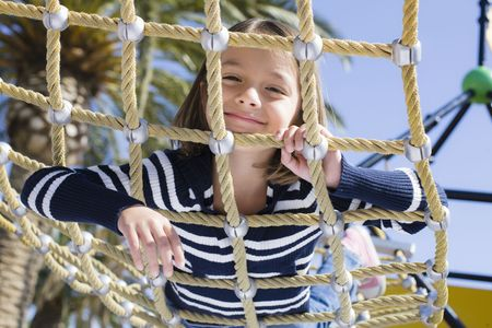 Young Girl on Stomach  Looking Through Rope on Hammock