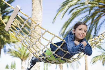 Teenage Girl Lying on Stomach on a Hammock in Park