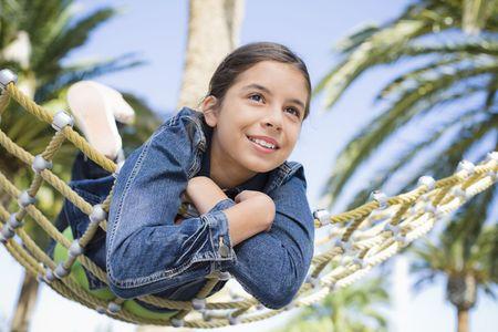 Smiling Teen Girl Lying on Hammock in a Park