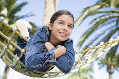 Smiling Teen Girl Lying on Hammock in a Park