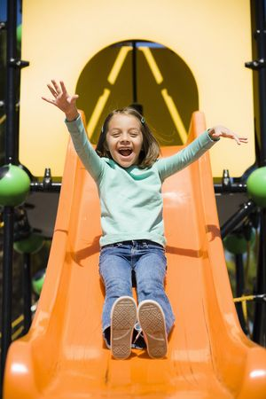 Smiling Young Girl in Park on a Slide Stock Photo