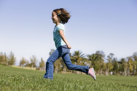 enfant qui court: Smiling Young Girl Running on Grass in Park