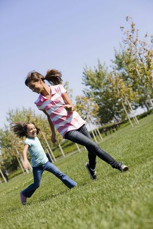 Two Hispanic Sisters Running on Grass in Park