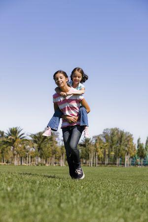 Teen Girl Giving a Piggyback Ride to Younger Sister Stock Photo - 5674783